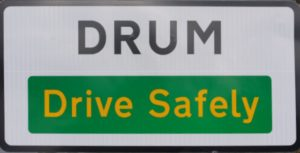 Drum street sign calling on motorists to drive safely